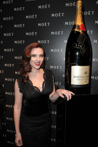 Scarlett Johansson signs a Moet & Chandon Nebuchadnezzar bottle, to be auctioned off for charity in support of OxfamÕs climate change program, at the Moet & Chandon: A Tribute to Cinema event in London, March 2009.